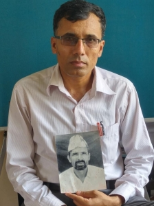 Suman Adhikari poses with a photo of his father Muktinath,