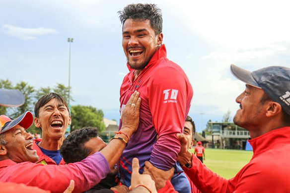 Nepal players rejoice after beating Canada in cricket.
