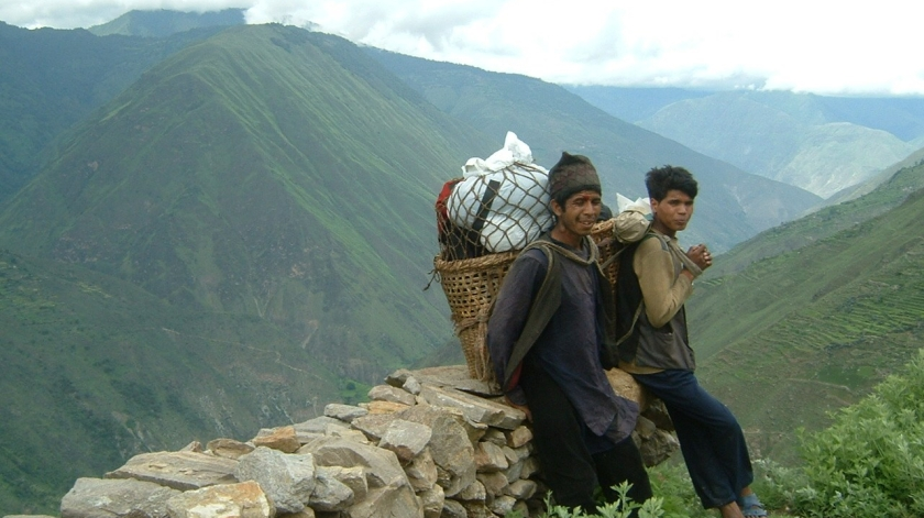 Two men heading home with rice delivered by the World Food Programme to Kolti, Bajura in 2006.